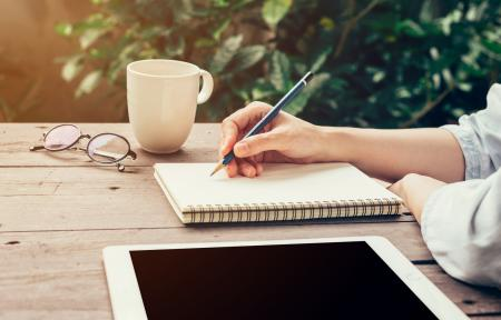 Young business woman hand with pencil writing on notebook. Woman hand with pencil writing on notebook and working at coffee shop.