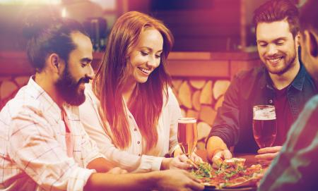 leisure, food and drinks, people and holidays concept - smiling friends eating pizza and drinking beer at restaurant or pizzeria
