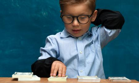 Cropped shot of little stylish boy counting money at workplace. Cute caucasian child imitating businessman or bookkeeper.
