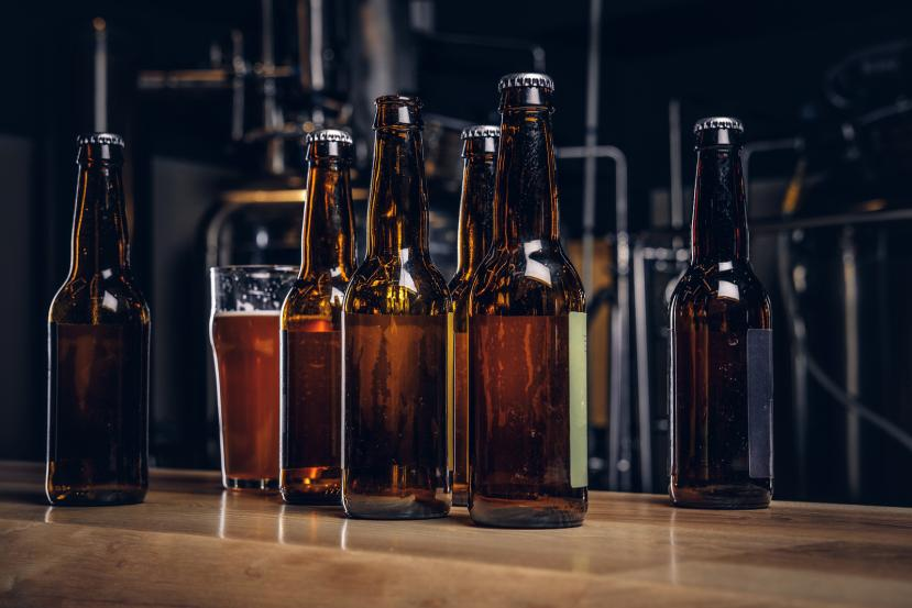 Bottles And Glass Of Craft Beer On Wooden Bar Counter At The Ind
