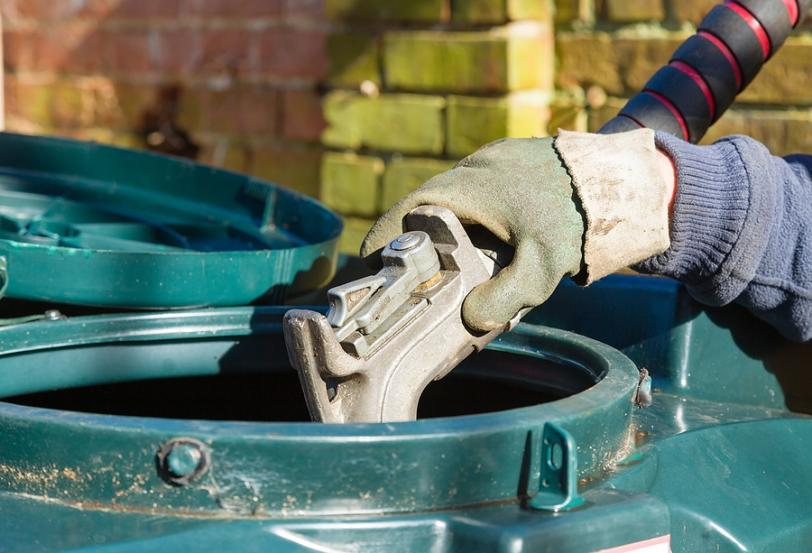 Closeup Of Man Filling A Bunded Oil Tank With Domestic Heating O