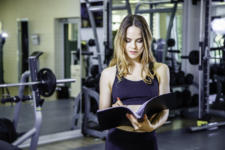 Young woman personal trainer writes the training plan in a noteb