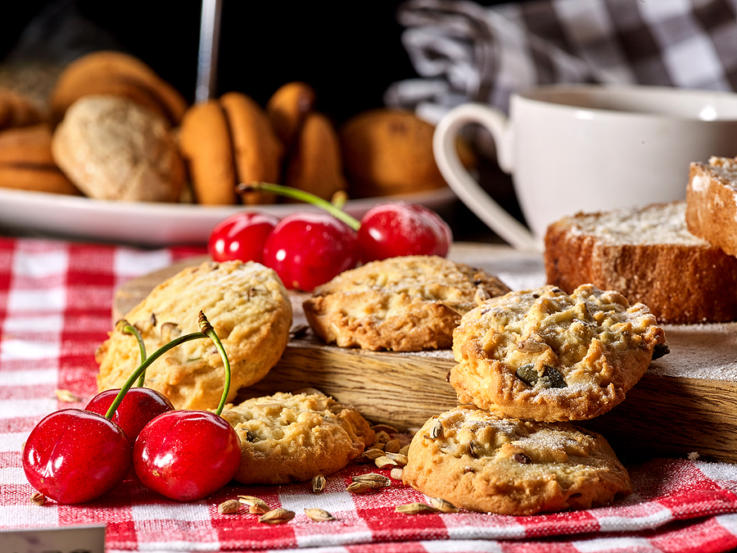Oatmeal cookies and cherry on kitchen cutting board gingham chec