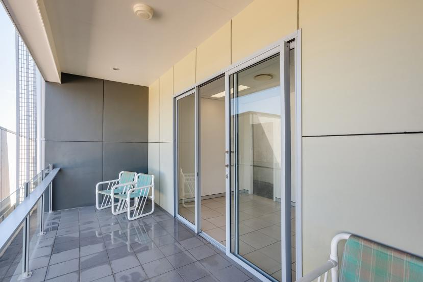 A Balcony With Contemporary Glass Rails And A Glass Sliding Door